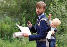 Businessman with smartphone and documents or contract closed eye. S from fatigue, his baby son in a sling on back, nature background stock photo