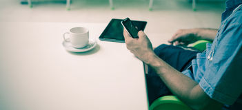 Businessman with smartphone in hands during coffee break Stock Photo
