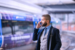 Businessman with smartphone, making a phone call, train platform. Hipster businessman with smartphone, making a phone call, walking at the train station platform Royalty Free Stock Image
