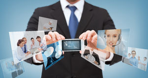Businessman with smartphone and news on screen Stock Images