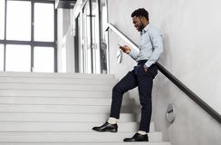 Businessman with smartphone at office stairs. Business, people and technology concept - african american businessman with smartphone at office stairs Royalty Free Stock Images