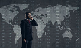 Businessman with smartphone standing over diagram. World map bac. Kground. Business, globalization, capitalism concept Royalty Free Stock Photo