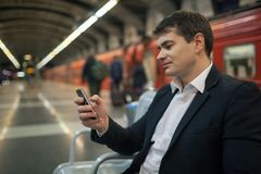 Businessman with smartphone in subway Stock Image