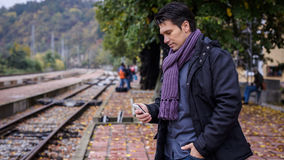 Businessman with smartphone at train station Royalty Free Stock Photography