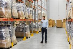 Businessman with smartphone at warehouse. Wholesale, logistic business, technology and people concept - businessman with smartphone at warehouse Stock Photo