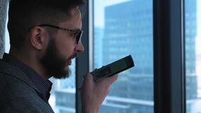 Businessman Smiles After Sending a Voice Message. Fashionable modern young man with a beard businessman writing a voice. Message on a smtrmfon. Located in a stock footage