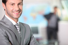 Businessman smiling with arms folded Stock Photography