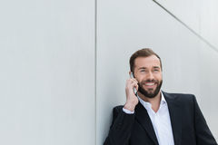 Businessman smiling as he chats on his mobile Royalty Free Stock Image