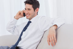 Businessman smiling and calling on sofa Royalty Free Stock Photos