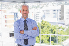 Businessman smiling at camera with arms crossed Royalty Free Stock Photography