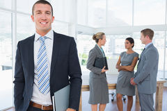 Businessman smiling at camera with colleagues behind him Stock Photos