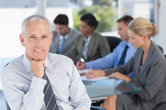 Businessman smiling at camera with colleagues behind Stock Photos