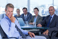 Businessman smiling at camera with colleagues behind Stock Images