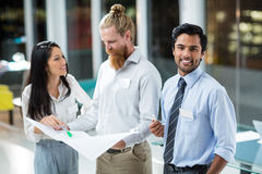 Businessman smiling at camera while colleagues discussing over blueprint Royalty Free Stock Photography