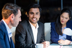 Businessman smiling at camera while colleagues looking at document Royalty Free Stock Images