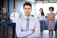 Businessman smiling at camera while her colleagues standing in background. Successful businessman smiling at camera while her colleagues standing behind him in Royalty Free Stock Photo