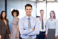 Businessman smiling at camera while his colleagues posing in background. Successful businessman smiling at camera with his arms crossed and his colleagues posing stock photography