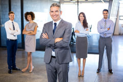 Businessman smiling at camera while his colleagues standing in background. Successful businessman smiling at camera while his colleagues standing behind him in stock photo