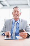 Businessman smiling at camera with his tablet and his phone Stock Image
