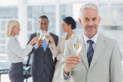 Businessman smiling at camera holding champagne Royalty Free Stock Image
