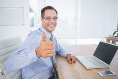 Businessman smiling at camera with thumbs up Royalty Free Stock Photography