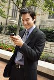 Businessman smiling at cell phone message. Stock Images