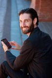 Businessman smiling with cell phone Stock Photos