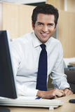 Businessman Smiling At Computer Desk Stock Photo