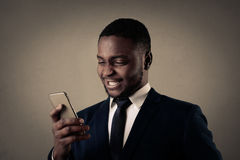 Businessman smiling and with his phone Stock Photography