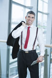 Businessman smiling and looking at camera with jacket over shoulder Royalty Free Stock Images