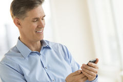 Businessman Smiling While Messaging Through Mobile Phone Stock Photos