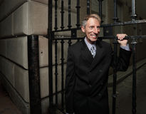 Businessman smiling by a metal gate Stock Photography