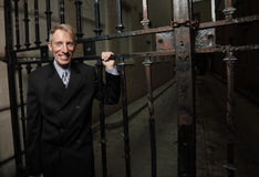 Businessman smiling by a metal gate Royalty Free Stock Image