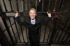 Businessman smiling by a metal gate Royalty Free Stock Photography