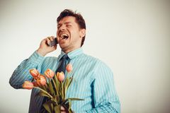 Businessman smiling while phoning and holding tulips Stock Image