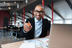 Businessman smiling and pointing at the working place Royalty Free Stock Image