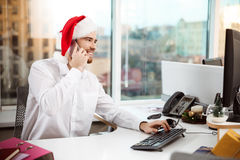 Businessman smiling speaking on phone at worplace  christmas day. Royalty Free Stock Images