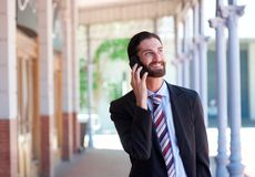 Businessman smiling and talking on mobile phone in town Royalty Free Stock Images