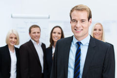 Businessman smiling with a team behind him Stock Photos