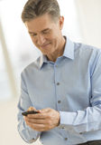 Businessman Smiling While Text Messaging Through Smart Phone Stock Images