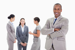 Businessman smiling with three co-workers talking in the backgro. Close-up of a businessman smiling and crossing his arms with three female co-workers talking in Stock Images