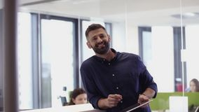 Businessman smiling to camera whilst using tablet in the office. Businessman smiling to camera whilst using tablet in typical office stock video
