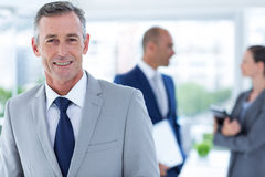 Businessman smiling  with two colleague behind him Royalty Free Stock Images