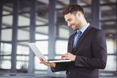 Businessman smiling while using laptop Stock Images