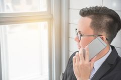 Businessman smiling while using mobile phone at office. Young asian businessman smiling while using mobile phone at office Royalty Free Stock Photo