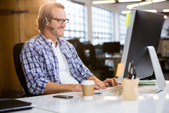 Businessman smiling while working on computer Royalty Free Stock Photos