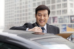 Businessman smiling, working outdoors on car Royalty Free Stock Image