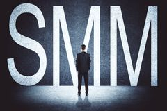 Businessman with SMM. Businessman with creative SMM text on concrete background. Social media and advertising concept stock images
