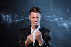 Businessman smoking with anger. Businessman smoking from his ears with anger stock images