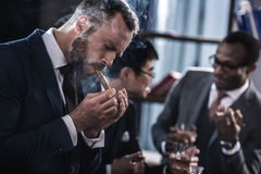 Businessman smoking cigar with multicultural business team. Spending time behind royalty free stock photo